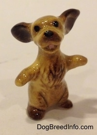 A tan with brown Cocker Spaniel figurine is sitting on its hind legs, it has its paws and ears out.