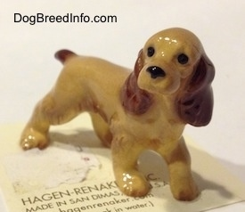 The front left side of a tan with brown ceramic Cocker Spaniel figurine. It has very detailed ears.