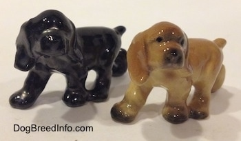 The front left side of two different ceramic Cocker Spaniel puppy figurines. They have short tails.