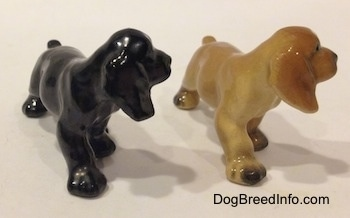 The front right side of two different ceramic Cocker Spaniel puppy figurinee. Both figurines are light on details.