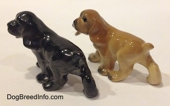 The back left side of two different ceramic Cocker Spaniel puppy figurines.