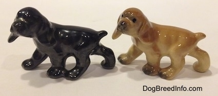 The left side of two different ceramic Cocker Spaniel puppy figurines. The right most figurine has more details than the left one.