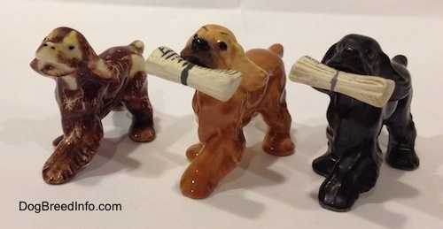 The front left side of three different Cocker Spaniel figurines.