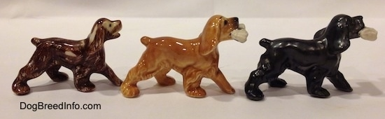 The right side of three different Cocker Spaniel figurines. The figurine furthest to the left has visible wear and tear.