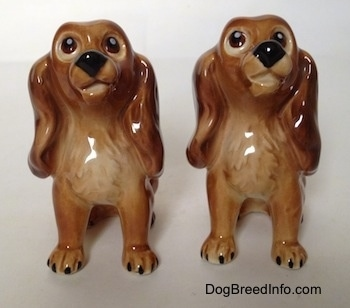 Two brown with tan Cocker Spaniel puppy figurines. The figurines have very detailed eyes and they are designed to look up.