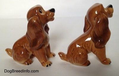 The right side of two brown and tan Cocker Spaniel puppy figurines. The figurines has a detailed ears.