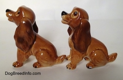 The left side of two brown and tan Cocker Spaniel puppy figurines. The figurines have short tails.