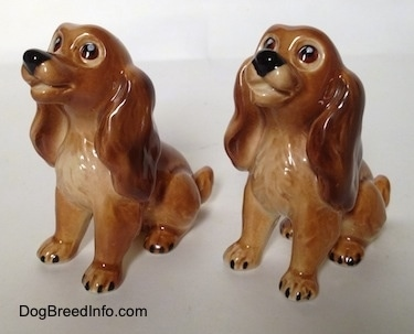 The front left side of two brown and tan Cocker Spaniel puppy figurines. The figurines look like they have smiles on them.