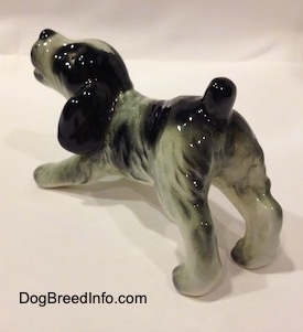 The back left side of a white and black Cocker Spaniel puppy figurine. It has lightly detailed eyes.