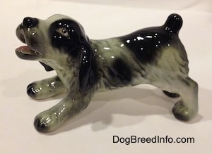 The left side of a white and black Cocker Spaniel puppy figurine. It has lightly detailed hair brushings.