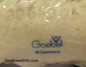 The underside of a white and black Cocker Spaniel puppy figurine the logo of Goebel W. Germany is displayed.