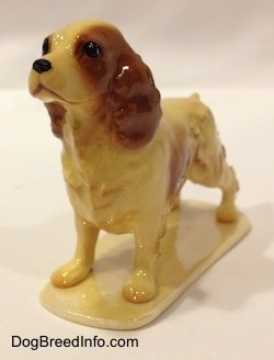 The front left side of a tan with brown ceramic Cocker Spaniel figurine. The hair on the figurine has fine details.