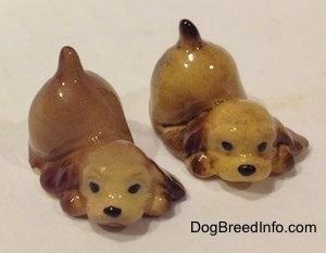 Two brown and tan ceramic Cocker Spaniel puppy figurines that are play bowing.