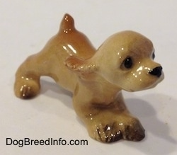 The front right side of a tan ceramic Cocker Spaniel puppy running figurine. It has fine eye details.