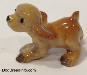 The left side of a tan ceramic Cocker Spaniel puppy running figurine. It is very glossy. The dog looks playful. The docked tail is short.