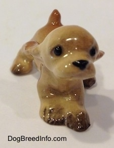 A tan ceramic Cocker Spaniel puppy running figurine. Its front paws are connected.