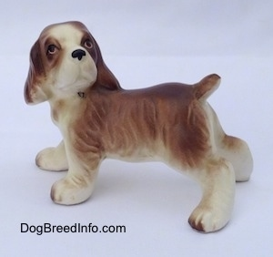 The left side of a brown and white ceramic Cocker Spaniel puppy figurine. It has great hair details.