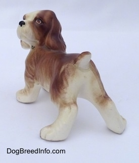 The back left side of a brown and white ceramic Cocker Spaniel puppy figurine. The figurine has a small tail.