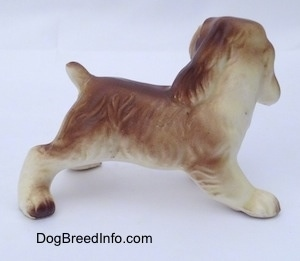 The right side of a brown and white ceramic Cocker Spaniel puppy figurine. The dog has long ears that hang down to the sides and a short cropped tail.