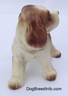 A brown and white ceramic Cocker Spaniel puppy figurine. The figurine is looking to the right and it has fine details on its ears.
