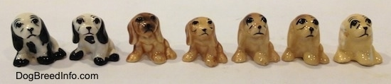 Seven color variations of a Cocker Spaniel figurine. The eyes on the figurines are detailed black circles.