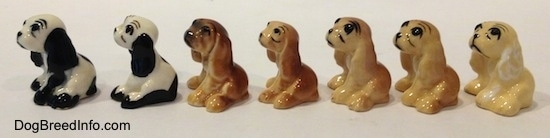 The left side of seven color variations of a Cocker Spaniel figurine. They are very glossy.