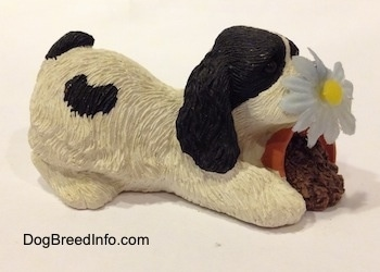 The right side of a sandicast black and white American Cocker Spaniel that is sniffing a flower out of a knocked over pot figurine.