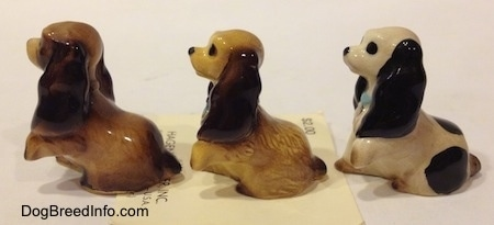 The left side of three different Cocker Spaniel puppy figurines.