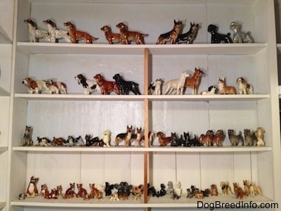 A collection of figurines on a white wall book shelf