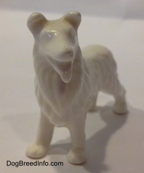 A white bone china Rough Collie figurine. The figurine is glossy.