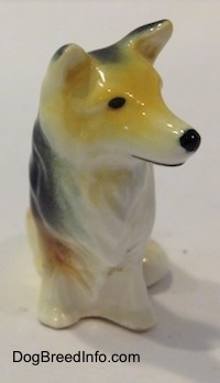 A figurine of a tan, black and white rough coated Collie dog that is in a sitting pose. The back of the figurines ears are black.