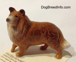 The left side of a brown with white Collie dog figurine that has great hair details.