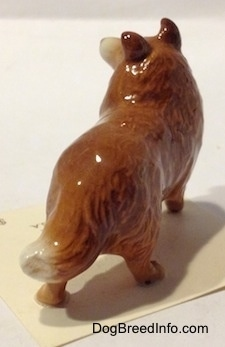The back right side of a brown with white Collie dog figurine. The figurine is glossy,
