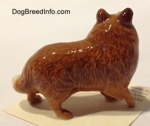 The right side of a Collie dog figurine. The figurine has detailed paws.