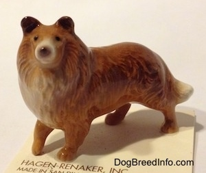 The left side of a figurine that is a Collie dog. The figurine has great face details.