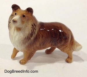The left side of a brown with white Collie dog figurine. The figurine has small black circles for eyes.