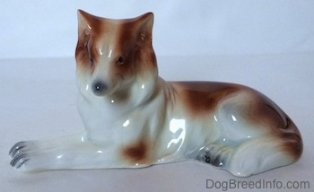 The left side of a brown and white Collie dog figurine in a lying down pose. The figurine has small black eyes for circles.