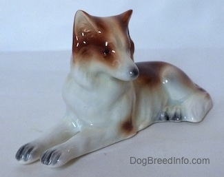 The front left side of figurine that is a brown and white Collie dog in a lying down pose. The figurine has few details in its paws. The nails on the paws are black.