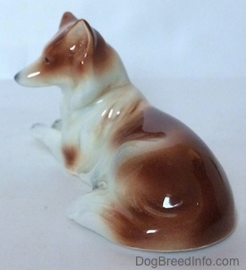 The back right side of a figurine that is a brown and white Collie dog in a lying down pose.