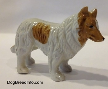 The right side of a white with tan bone chine Rough Collie figurine. The figurine has hair details along its body.
