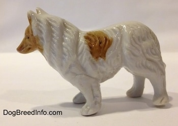 The left side of a bone china figurine that is a white with tan Rough Collie. The figurine has fine paw details.