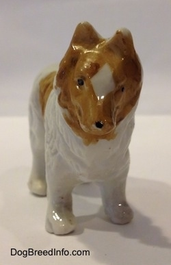 A bone chine white with tan Rough Collie figurine. The figurine has a black dot for a nose.