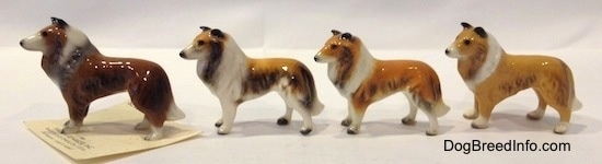 The left side of four different variations of a Collie dog figurine. All of the figurines have black circles for eyes.