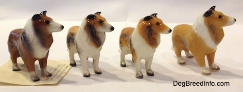 The front right side of figurines that are variations of a Collie dog. All of the figurines hace black nails on the paws.