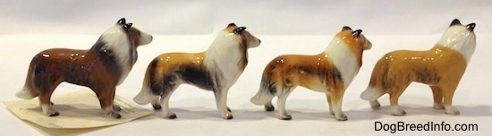 The right side of four Collie dog figurine variations. All of the figurines have white paws.