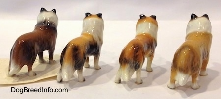 The back right side of four Collie dog figurine variations. The tips of each of the figurines tails are black.