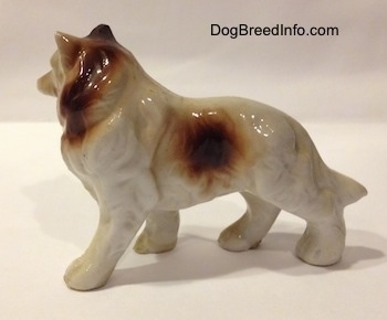The left side of a porcelain figurine that is a brown and white Rough Collie. The figurine has fine fur details.