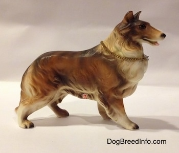 The right side of a ceramic Rough Collie figurine that is brown, black and white. There is a sticker on the side of a figurine.