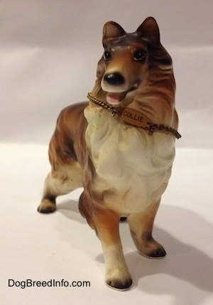 A ceramic brown, black and white Rough Collie figurine that is wearing a chain ID that reads - COLLIE - on it.