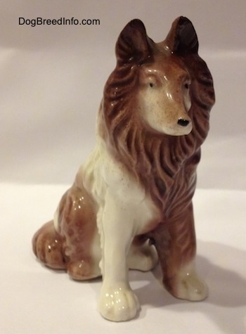 A brown and white porcelain Rough Collie figurine in a sitting pose. The figurine has black circles for eyes.